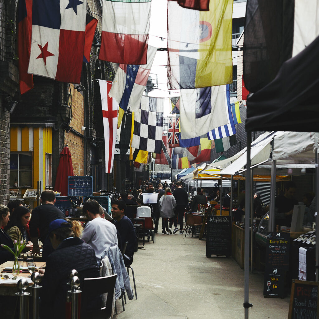 Narrow street lined with tables and food stalls, people sitting at the tables. Flags of different countries hang above the street.
