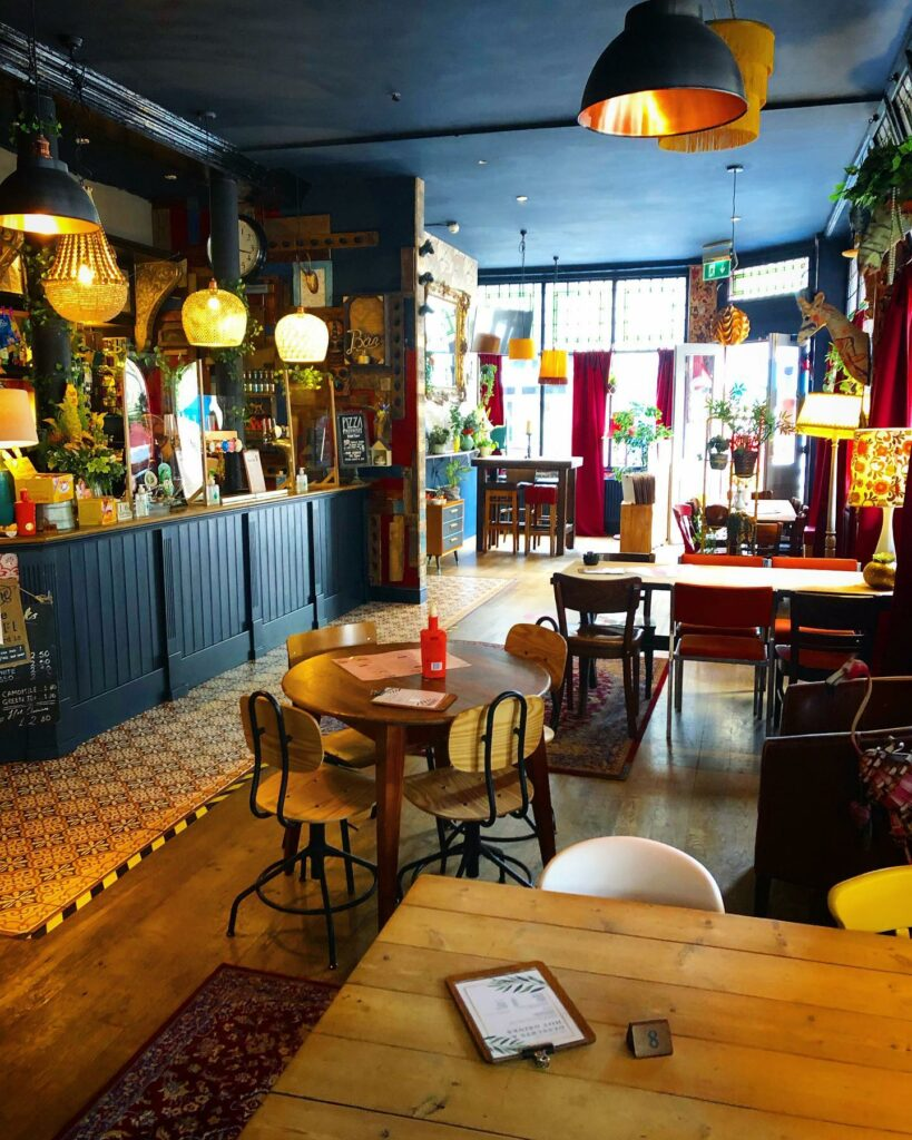 Colourful pub interior. Carpets on the floors. A lot of plants, colourful lamp shades and a bar.