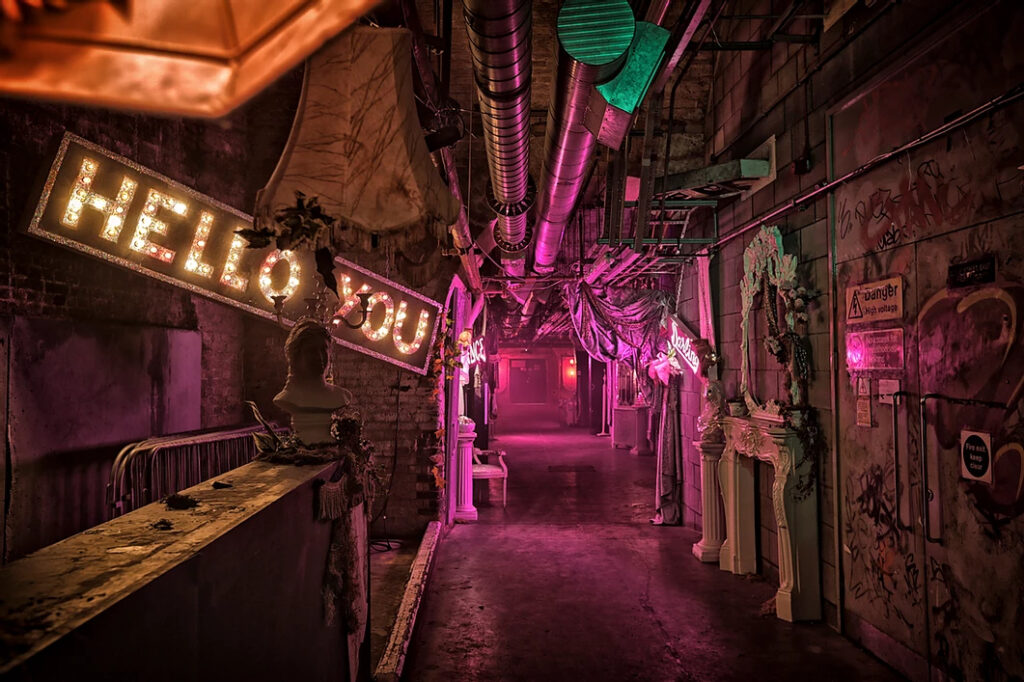 Rundown hallway with pink light and Hello You neon sign
