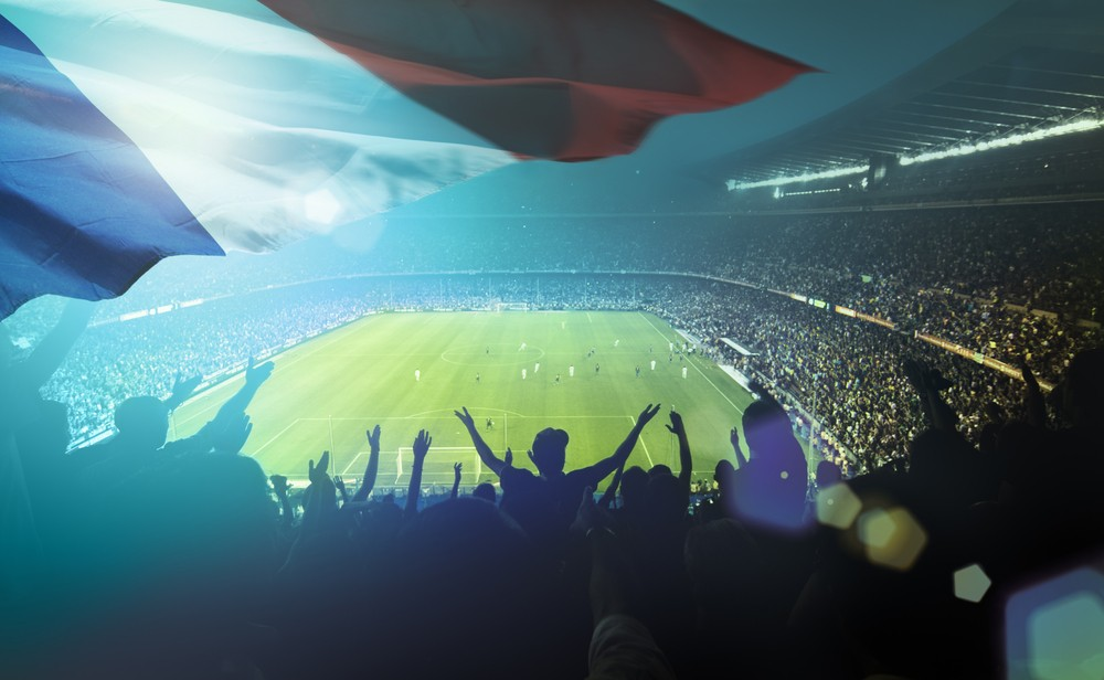 A stadium full of cheering fans, with a French flag waving in front of the camera.