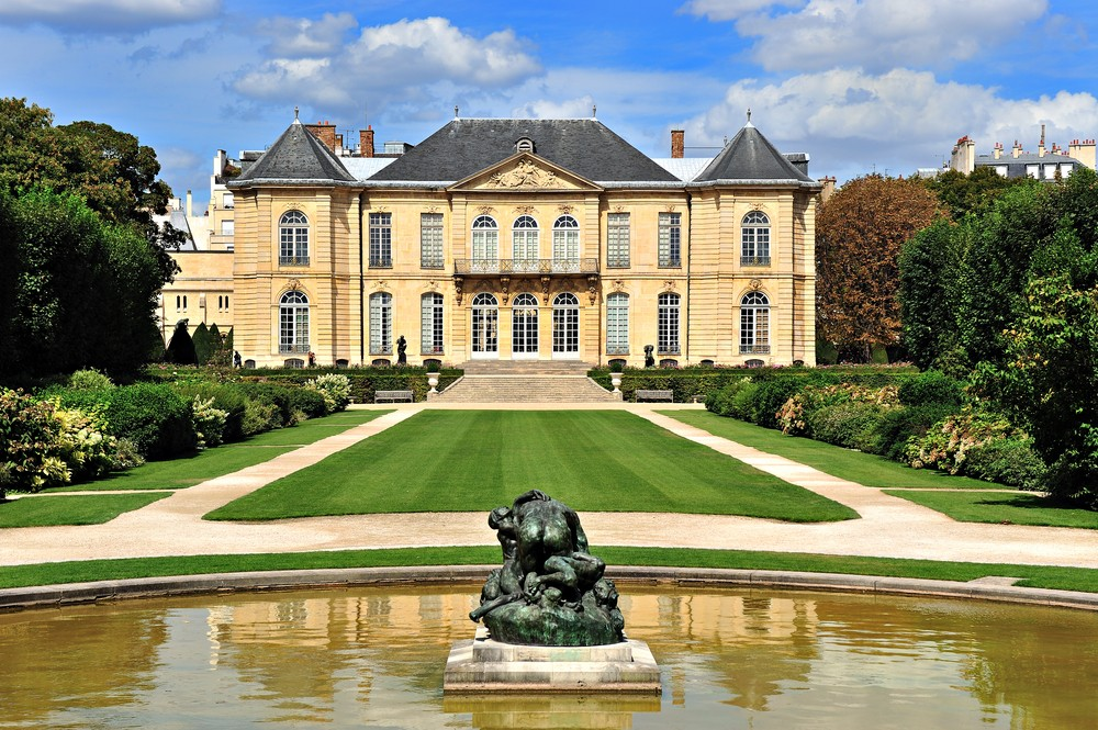 Exterior view of the Musée Rodin with manicured lawns and a Rodin statue.