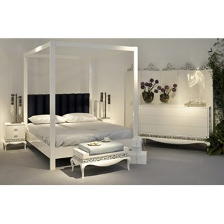 Grand glossy white four poster bed with black velvet headboard