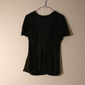 Tshirt med peplum fra Monki i str. 38. D - Århus - Tshirt med peplum fra Monki i str. 38. Den er sort og har nogle store striber i forskellige sorte stoffer. Der er lynlås bagpå - Århus