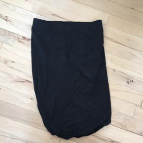 Nederdel fra Moos Copenhagen. Nederdelen - Esbjerg - Nederdel fra Moos Copenhagen. Nederdelen er mørke grå og har i den nederstedel et lille twist, hvor nederdelen folder sig, når men tager den på. - Esbjerg