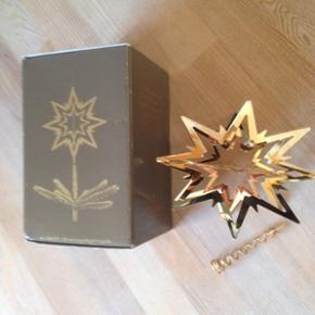 Georg Jensen Topstjerne i guld 180mm med - Frederikshavn - Georg Jensen Topstjerne i guld 180mm med rødt bånd til ophæng og spiral til at sætte på juletræet. Som ny. - Frederikshavn