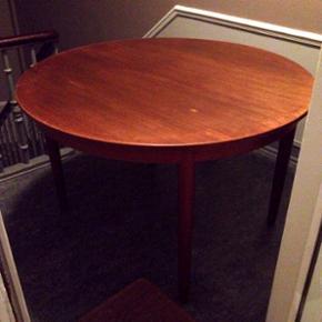 Rundt teaktræsbord med en tillægsplade - København - Rundt teaktræsbord med en tillægsplade. Standen er fin, men med enkelte brugsspor, en overfladisk ridse og et mindre brændemærke - se billeder. Pladen er en anelse lysere i nuancen. Dette kan sagtens udbedres med lidt snilde. Omkreds ca.  - København