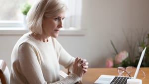 Common Mistakes When Buying Medical Alert System for Seniors woman at computer thinking