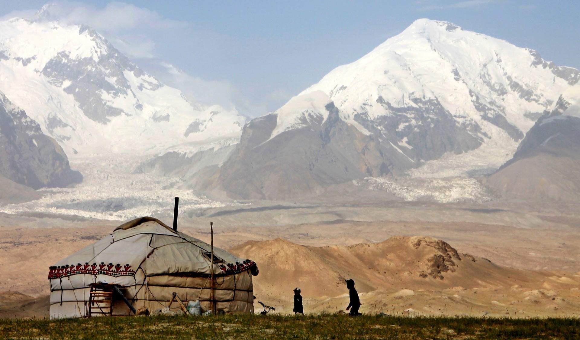 Children playing outside yurt in Tajikistan, China