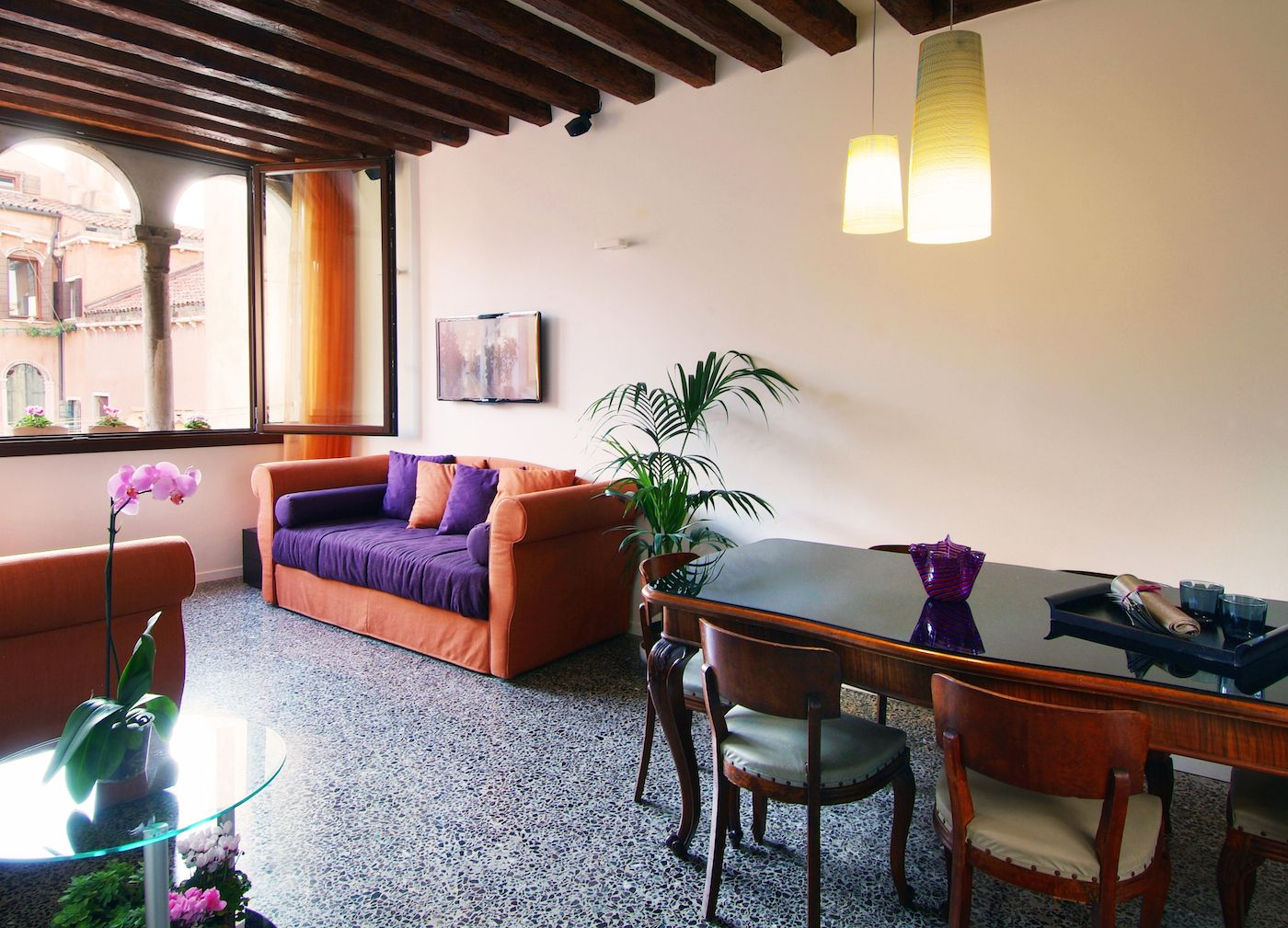 spacious living room with wooden beams, terrazzo flooring and the authentic trifora window
