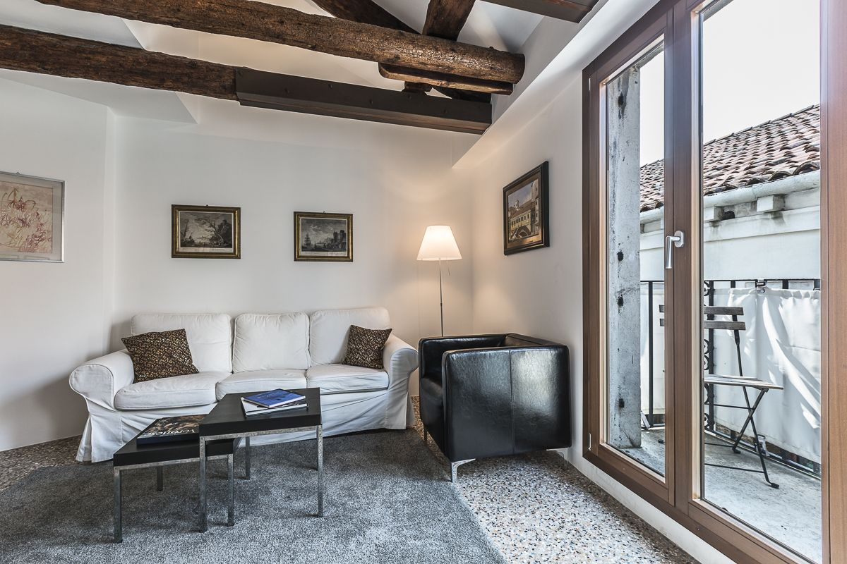 the bright and cozy living room of the Guardi apartment with balcony