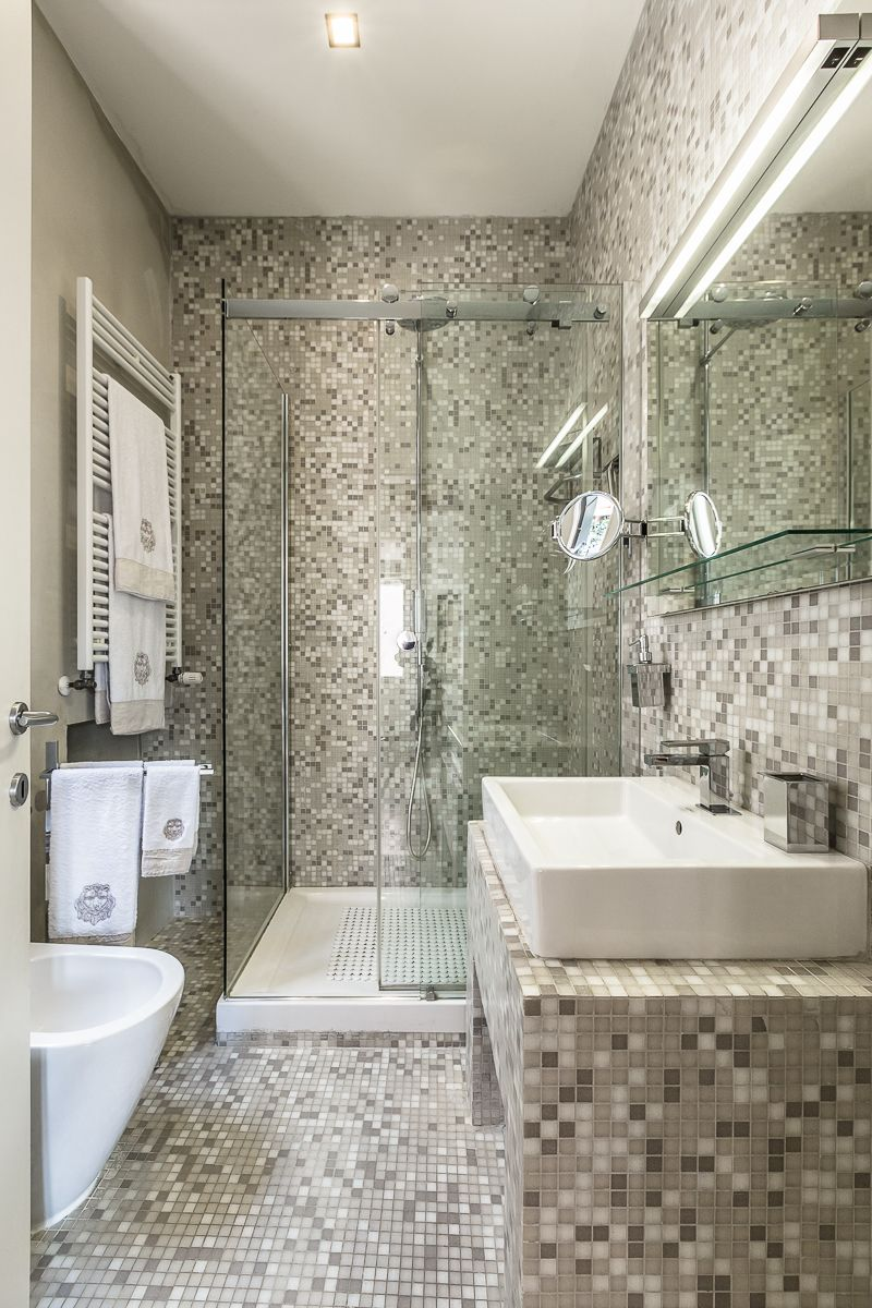 the mosaic en-suite bathroom features a luxurious shower cabin