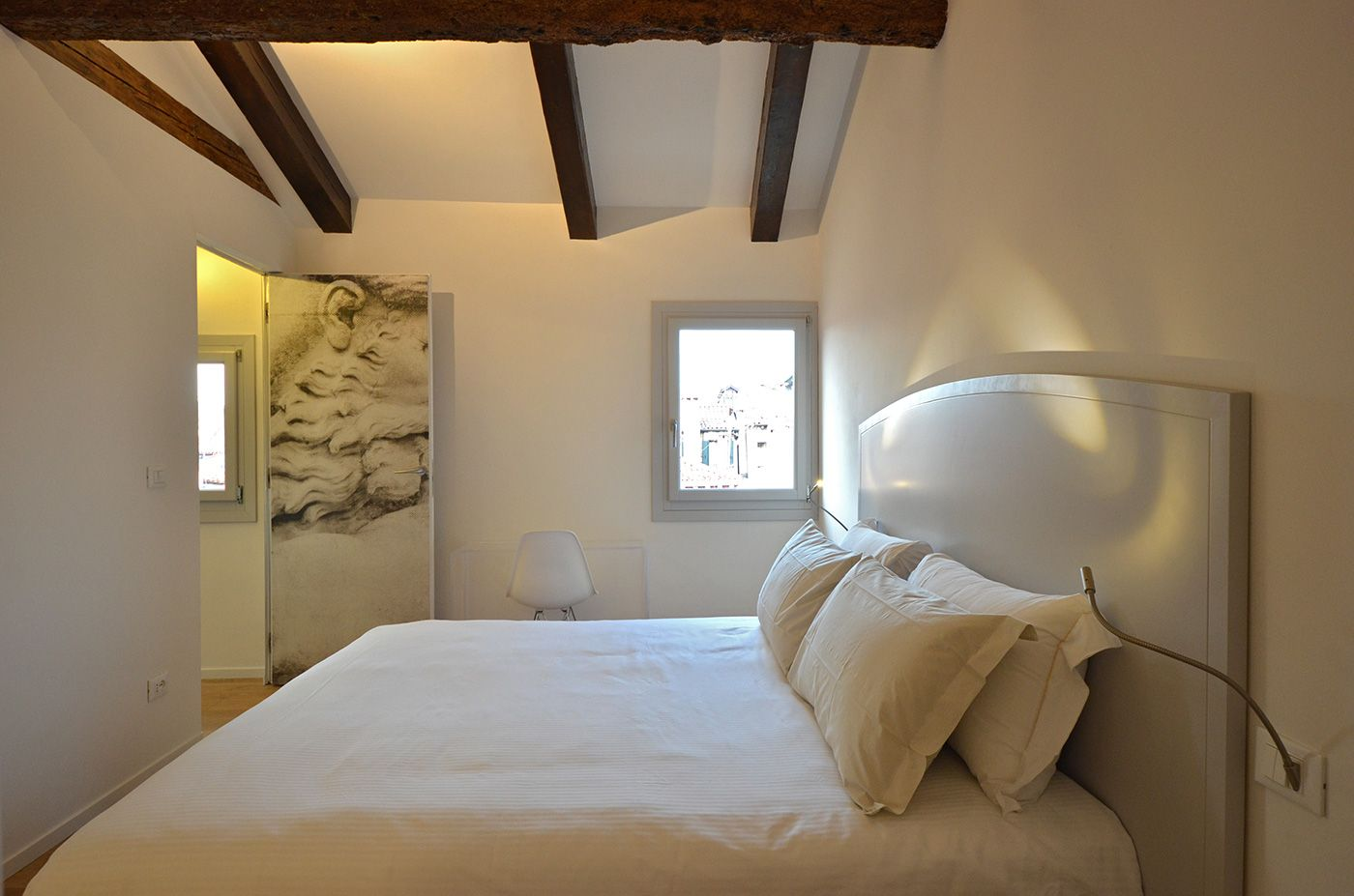 the bedroom features view on the roof-tops and wooden beams