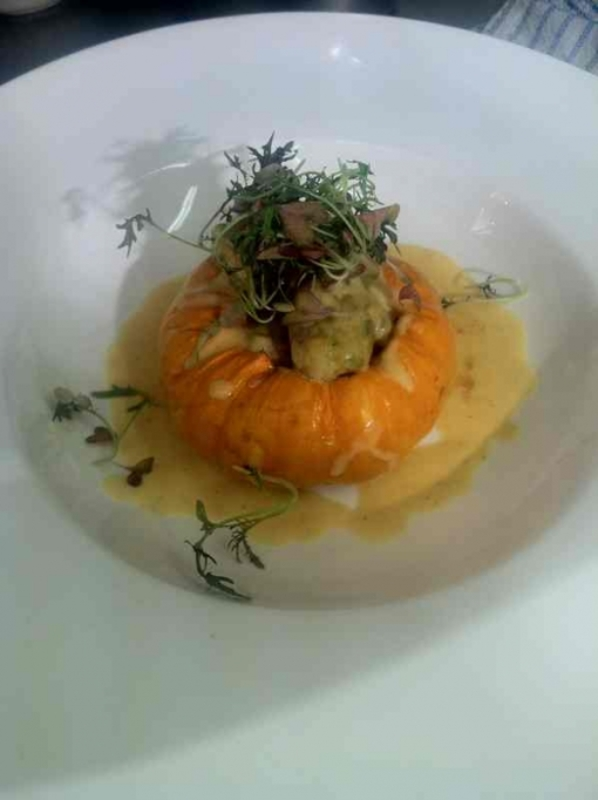 Pumpkin and thyme gnocchi stuffed in a mini baked pumpkin topped with micro herb salad