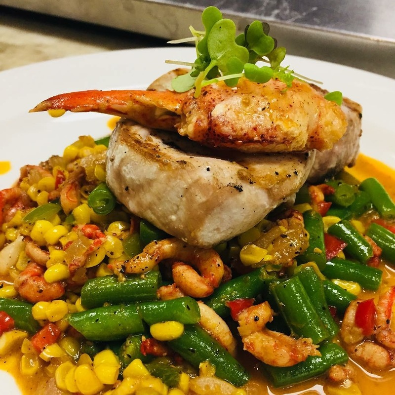 Grilled swordfish steak served over lobster succotash and corn broth