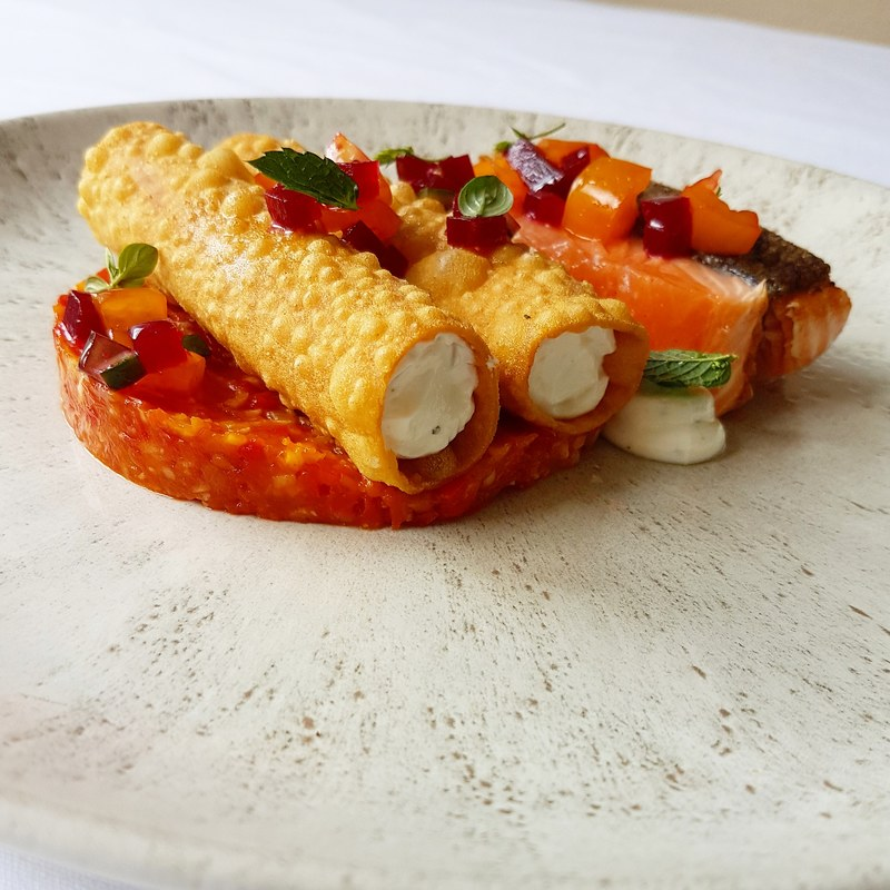 Seared salmon with crispy cannelloni filled with cured salmon, beetroot, and goats cheese, tomato fondue