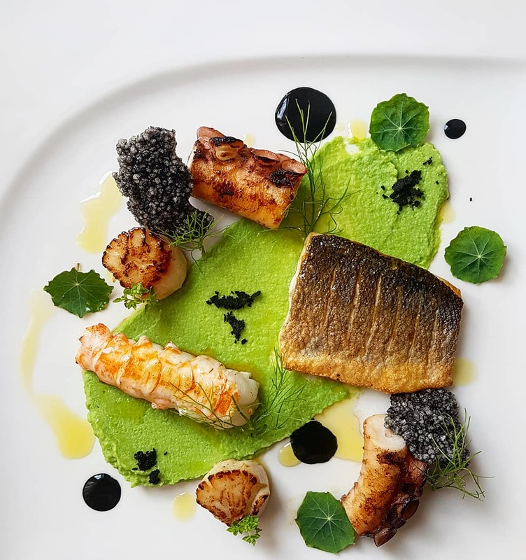 Pan seared sea bass•24 h sous vide grilled octopus•butter basted langoustine and scallops•pea fennel purre•black garlic aioli..