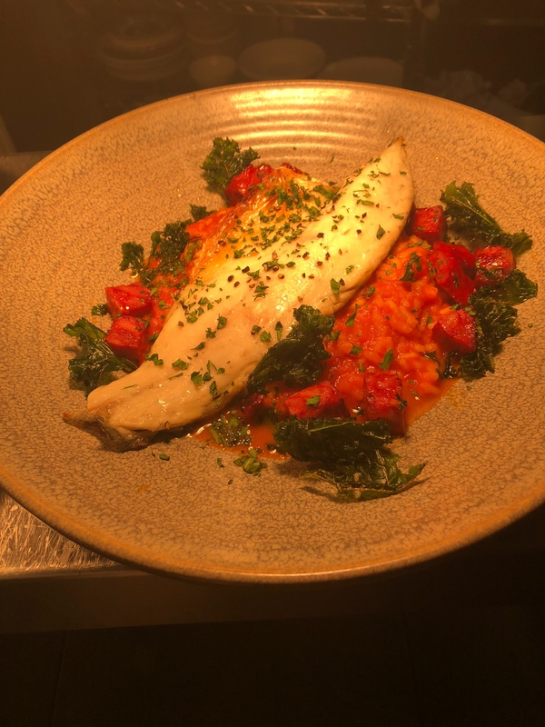 Pan fried sea bass on spicy chorizo tomato risotto and crispy kale