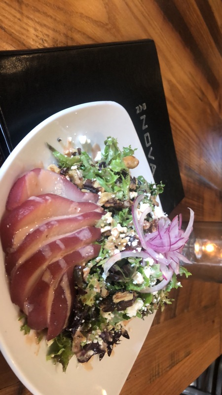 Poached pear salad with a red wine cherry goat cheese dressing, feta, toasted walnuts, and shaven red onions on Arcadian mixed greens