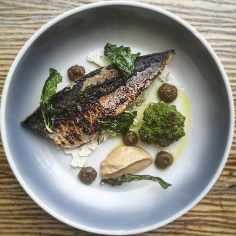 Lightly cured and charred line caught mackerel, smoked cauliflower purée, butter roast romenesco, shaved raw cauliflower , cauliflower leaf crisp, raisen and caper relish.