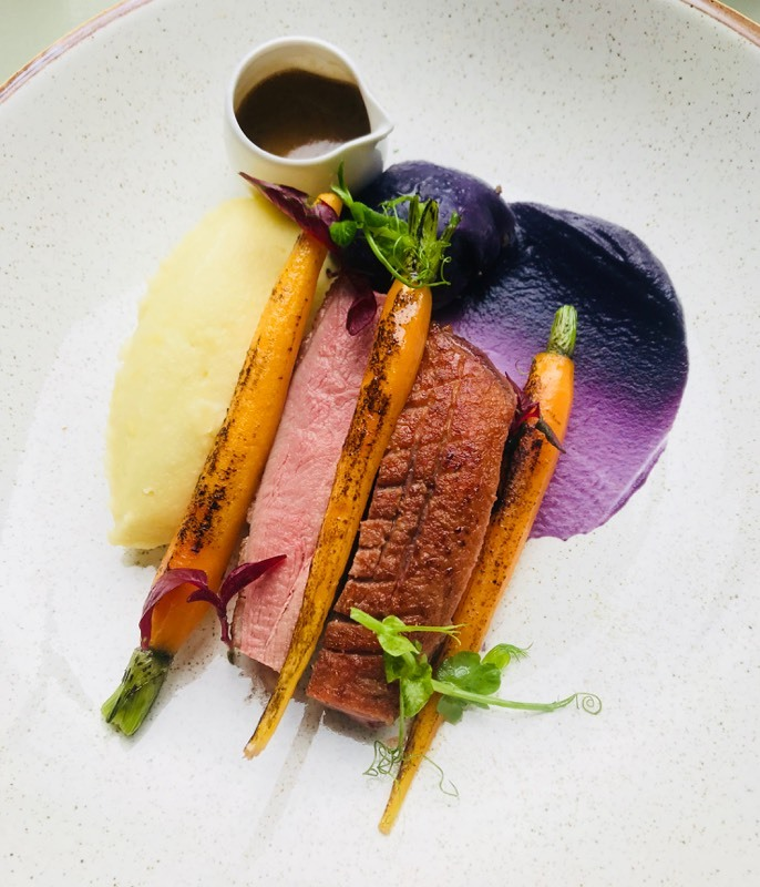 Duck breast, confit duck leg wrapped in red cabbage, charred carrots, mash, jus.