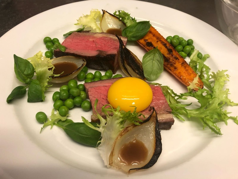 Coffee rubbed flank steak, peas, charred onions and carrot, cured egg yolk.