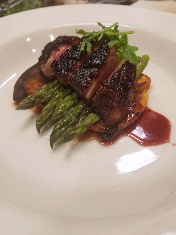 Pan seared duck breast over roasted sweet potatoes and asparagus, topped with a pomegranate demi glace