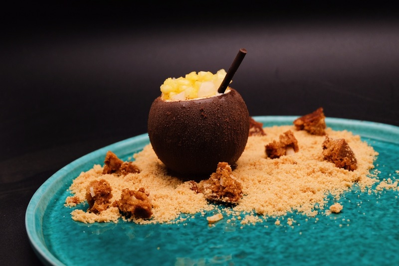- salted caramel centered, chocolate coated coconut cream bavaroise - palm sugar blondie - lime sand - pineapple & nata de coco
