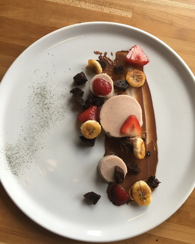 Banana split panacota , compressed champagne strawberries , caramelized bananas , browni crumble and mint dust .