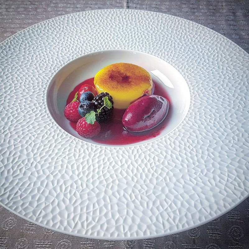 Caramelised lemon custard. Fresh mixed berries, almond crumble, chilled berry consomme, berry sorbet.