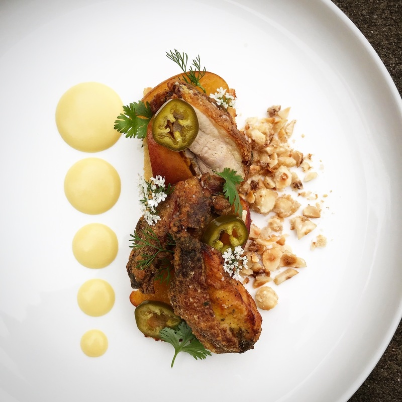 Fried chicken with corn purée and brown sugar compressed peaches, pickled jalapeños, fried hazelnut