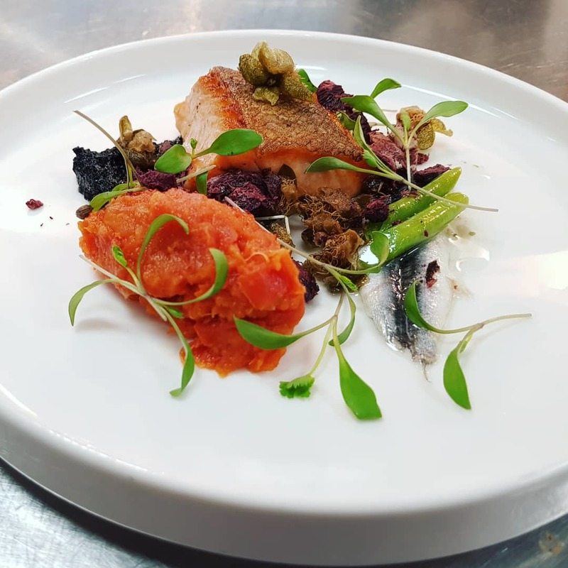 Trout nicoise in a bed of grated yolks. *Compressed nicoise and kalamata olives puree,nicoise crumbles, blanched and light pickle French beans and anchovy, crispy capers and 16hours slow reduction of red grapes cherry tomatoes tepanade and chervil cress