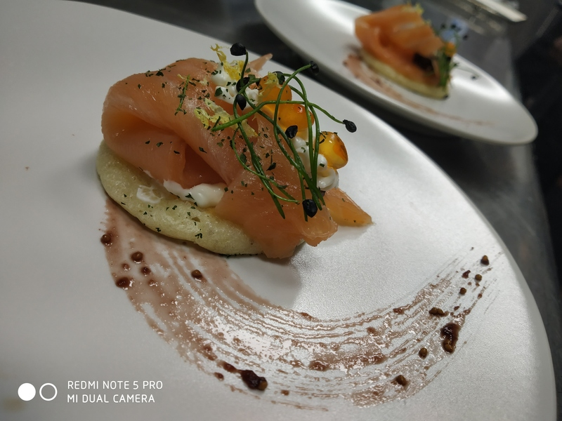 Smoked salmon on blini with salmon caviar, cream cheese, fig compote, lemon zest and parsley dust