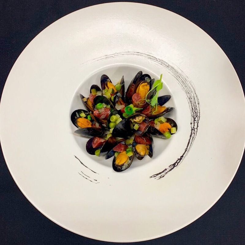 Mussels with sausages and vegetables with light zucchini sauce and mint petals
