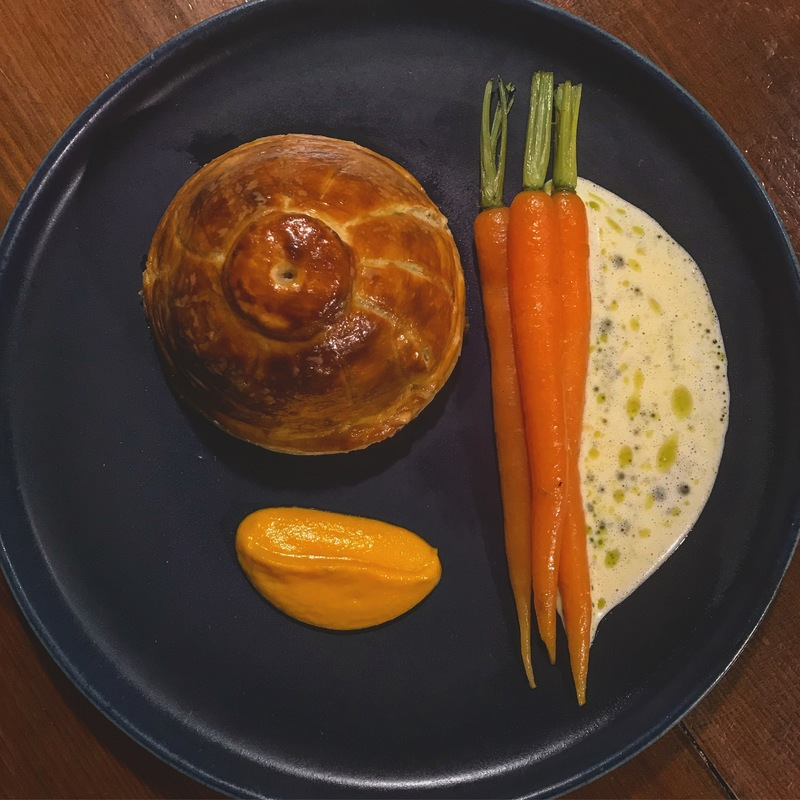 24h braised ox-cheek pithivier with a baby turnip fondant core, carrot cream, baby carrots, sauerkraut, mustard, and herb oil split cream