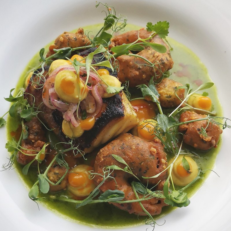 Pan fried cured coley, pea, roast garlic, lime and coconut cream, mussel, calm and prawn pakora, curry cauliflour puree, fermented mango and lime gel, spiced onions.