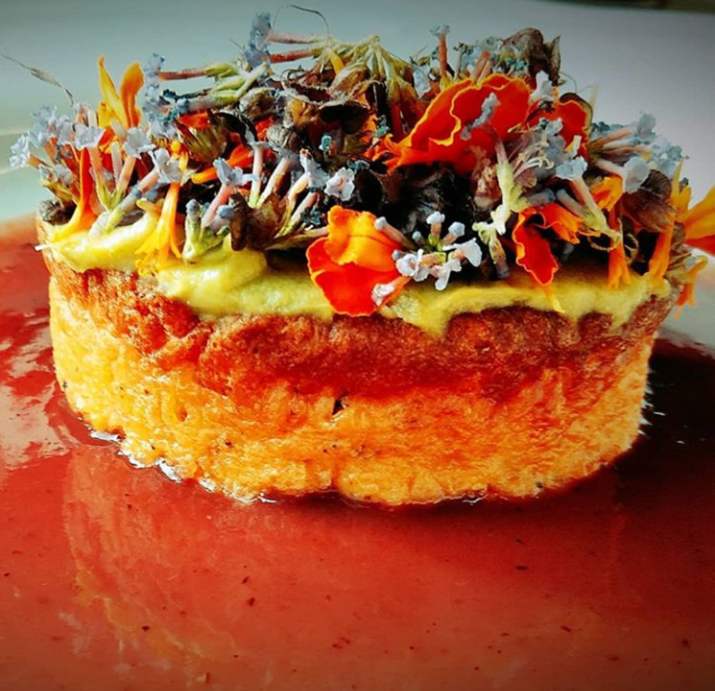 Okonomiyaki, savory pancake filled with octopus cabbage and scallion. Topped with spicy avocado mayonnaise and edible flowers, sauce is blackberry and ginger.