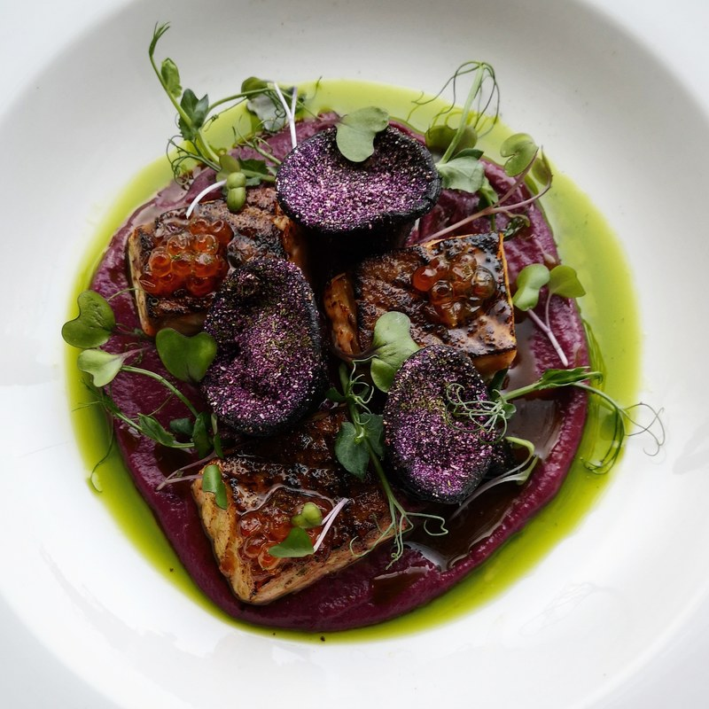 Squid ink tortellini, stuffed with cured salmon belly, tarragon and garlic, charred salmon, red cabbage purée, powder and shoots, smoked parsley oil, honey and salmon keta dressing.