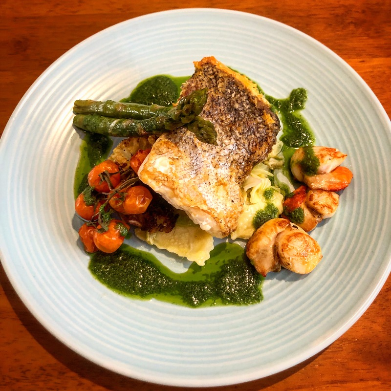 Roasted day boat hake, hand dived scallops, cherry vine tomatoes, asparagus, asparagus ravioli, sweet heart cabbage, wild garlic pesto