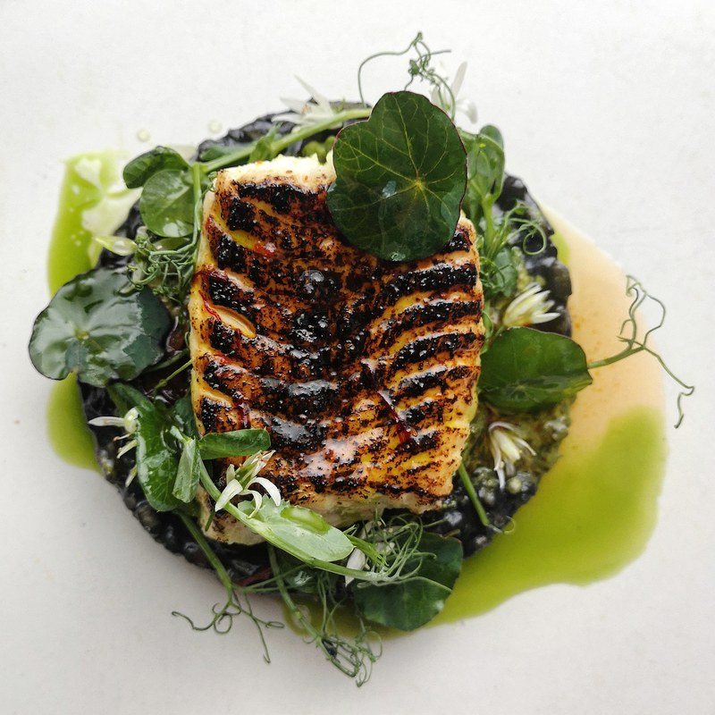 Beautiful rock turbot grilled, charred and glazed with lemon chilli and saffron oil on squid ink risotto, wild garlic and almond pesto, balsamic pickled onions, wild garlic oil, pea shoots and nasturtiums.