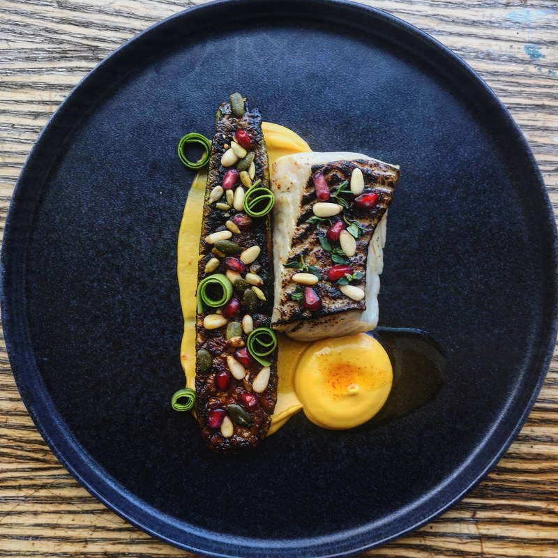 Cured and charred coley, roast spiced courgette, both glazed with sweet pepper and roast chicken butter, sweet potato, chilli and saffron purée, pine nuts and pomegranate.
