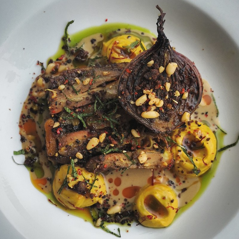 Spiced, pressed lamb belly with apricots and raisens, saffron and cauliflour puree, lamb fat roast onion, pine nuts and crispy minced lamb, lamb sauce and oils.