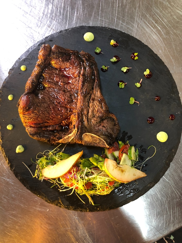T-bone steak with tomato salad with cucumbers and mix salad seasoned with switch sauce and caramelized pear