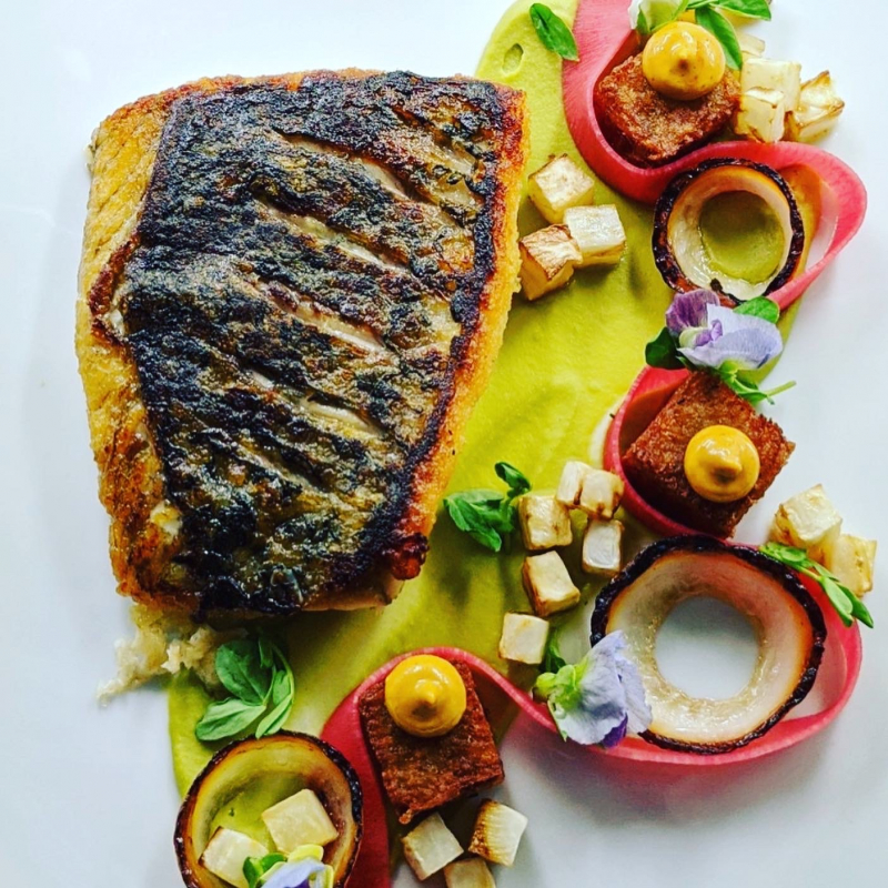 Crispy skin barramundi, pea puree, crispy potato, tomato aoili, pickled radish, celery root, charred onion, pea blossom.