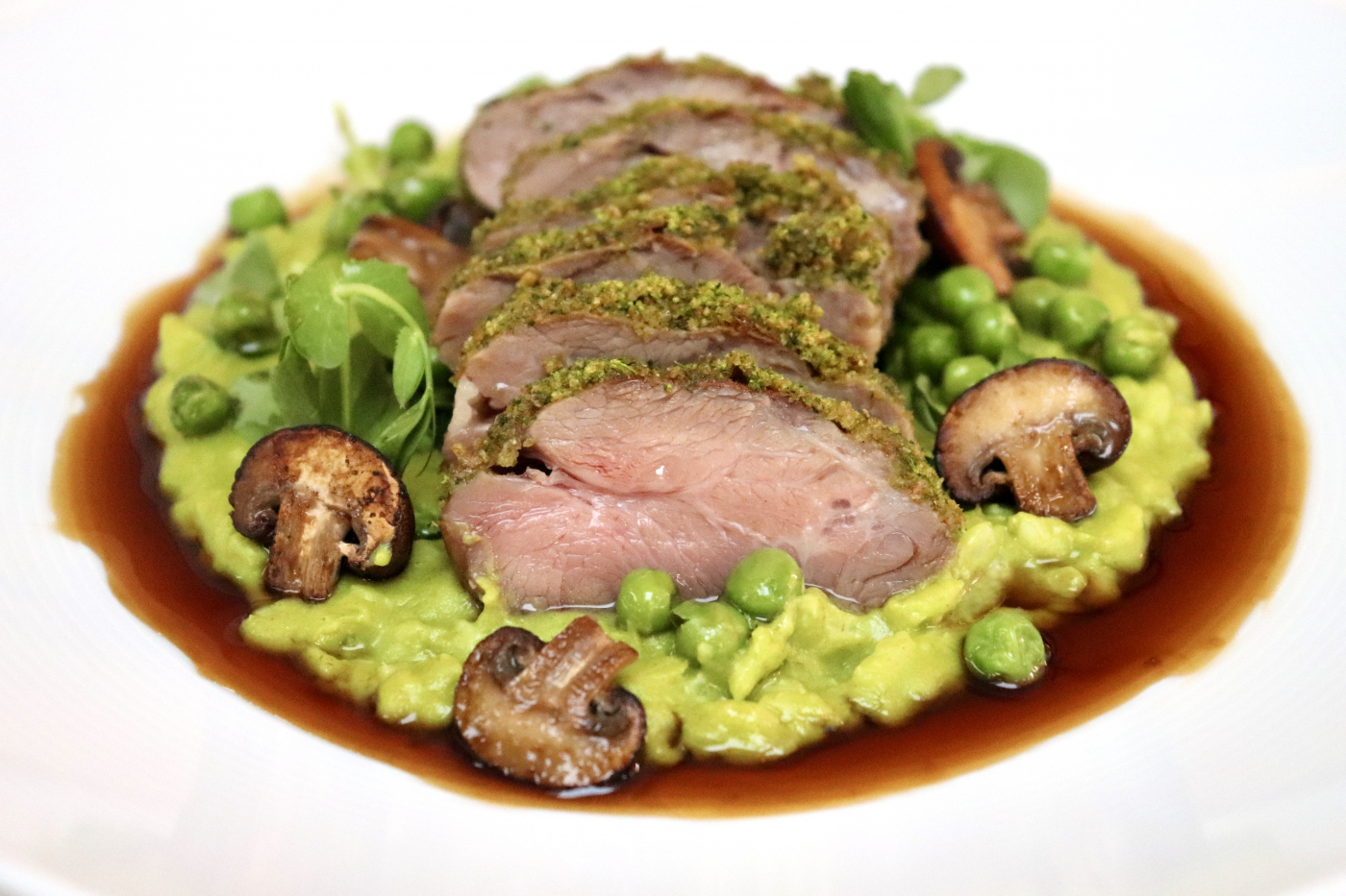 Herb-crusted neck fillet of lamb. Pea risotto, pea shoots and fresh garden peas. Buttered spinach and pan-fried chestnut mushrooms. Lamb jus.