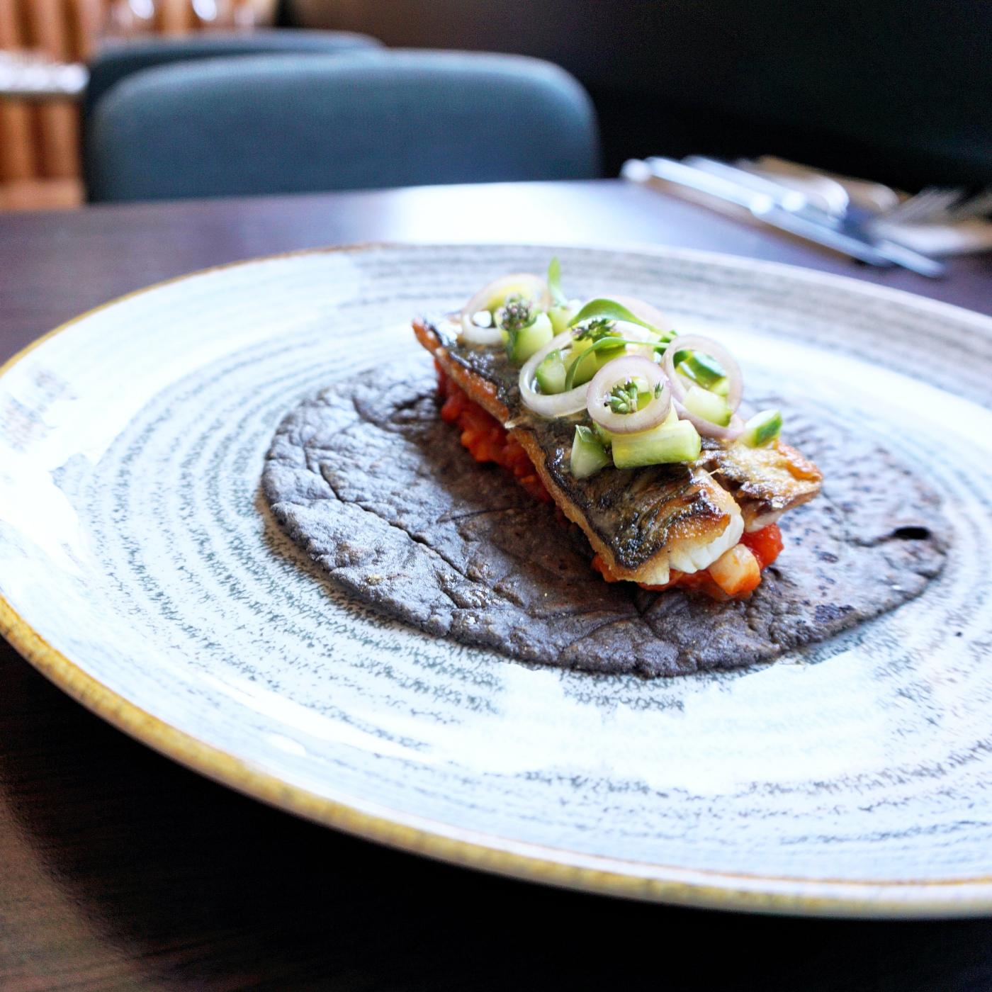 Seared mackerel with squid ink tortilla, tomato compote, soused  cucumbers