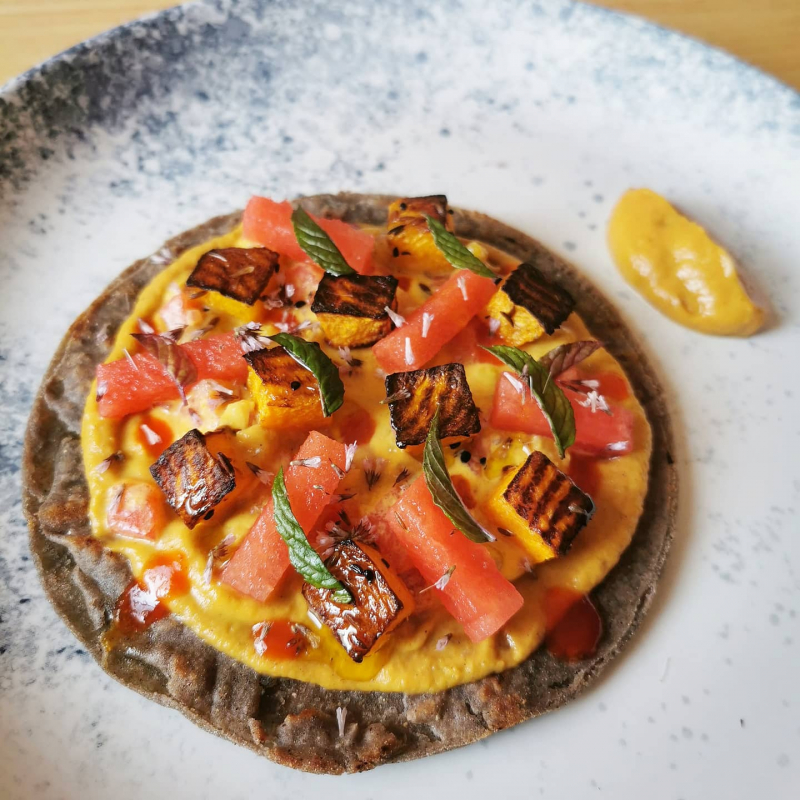Roast squash, squash and chipolte puree, watermelon, corn and yellow tomato salsa, salted watermelon, fermented chilli, chocolate mint on a blue corn tortilla.