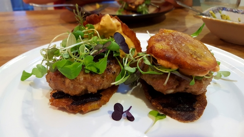 plantain sliders... double fried plantain chips, the citrus flavour of black garlic smeared on like butter, cumin chicken patties, a spicy microgreen mix & a sambal oelek mayo.