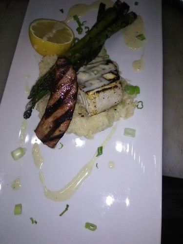 Grilled andouille sausage and halibut w/ créole grits and oak smoked asparagus topped w buerre blanc butter sauce.