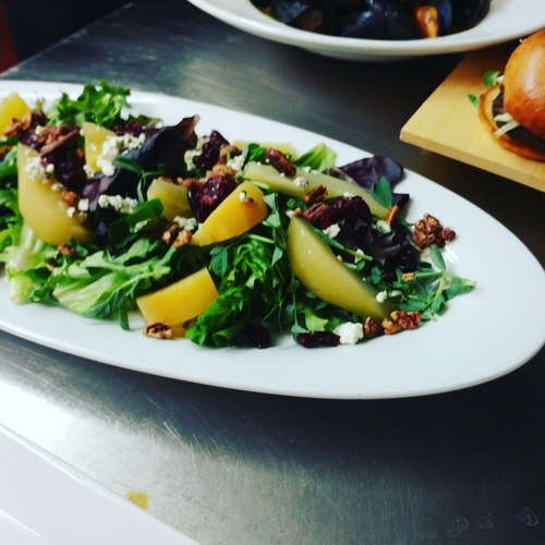Poached pear and golden beets over greens with herb chevre candied walnuts dried cranberries
