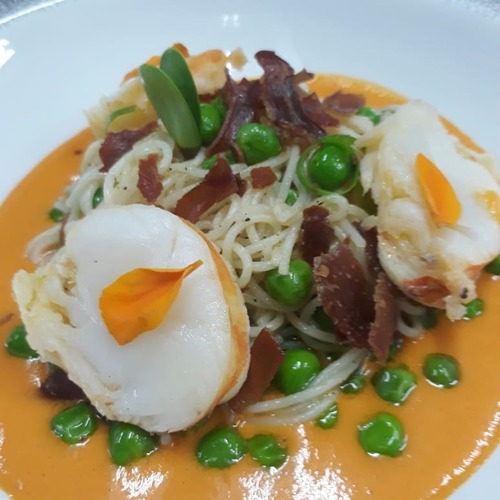 Lemon poached lobster on angel hair pasta with green peas and crispy pancett in bell pepper coulis